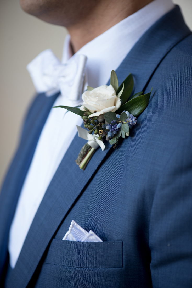 White rose boutonniere on blue suit with white bow-tie and pocket square
