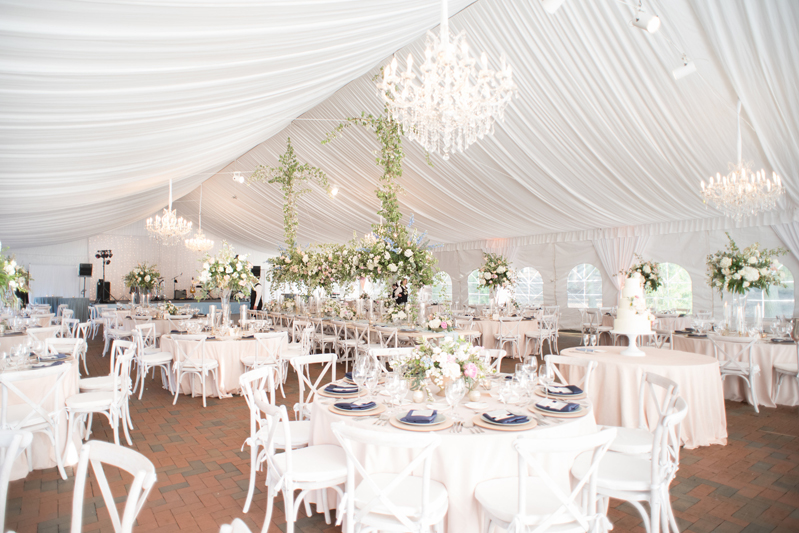 Tented reception with white chandeliers, tables and chairs