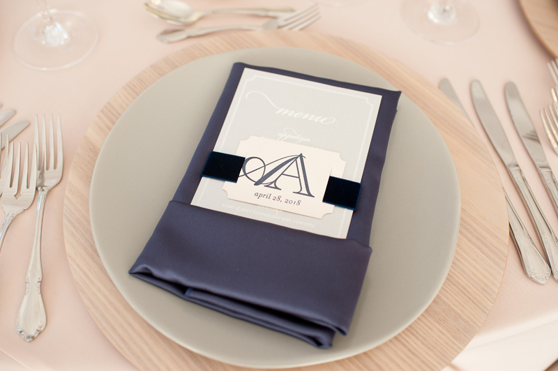 Navy blue place setting on wooden chargers