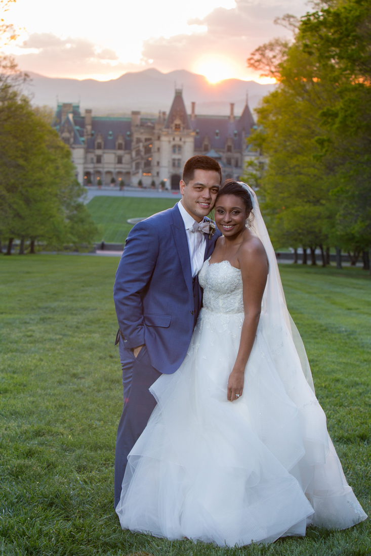 Bride and groom in front of Biltmore Estate at sunset.