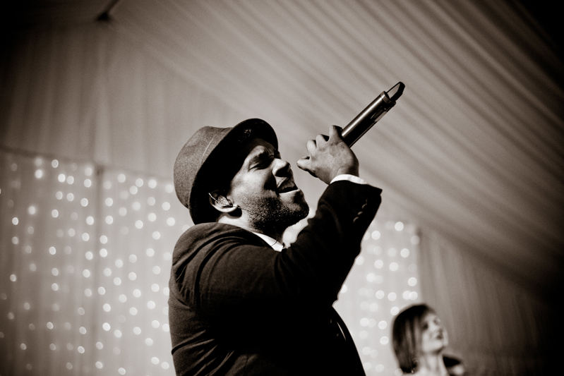 Male vocalist with hat singing into microphone.