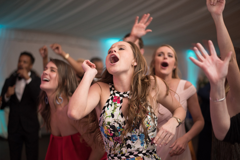 Group of females dancing and singing on dance floor during wedding reception.