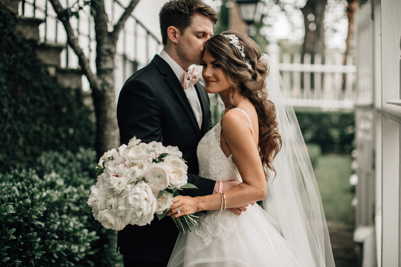 Groom kissing bride's head after ceremony