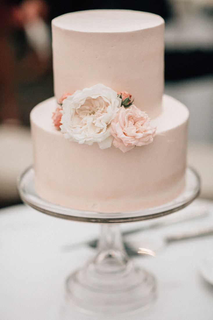 pink two-tiered wedding cake with flowers