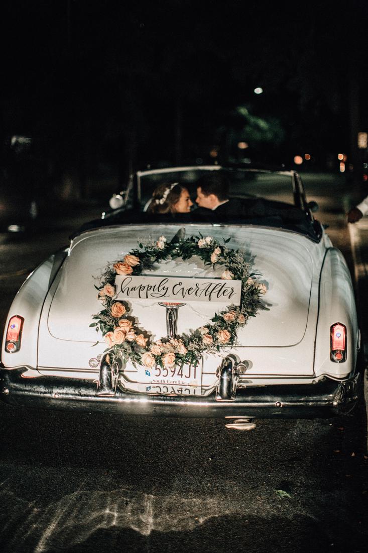 bride and groom leaving wedding in vintage car